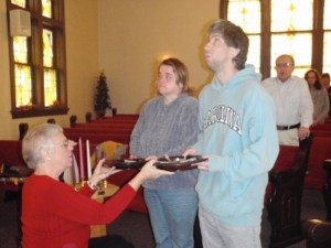 The Rev. Sue Montgomery hands out the offering plates during one of her Tuesday morning services that regularly includes about a dozen men and women with developmental disabilities from the Nickleville area.