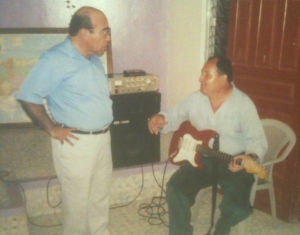 Rev. Nering Huete (standing) talks with a musician from his church, La Iglesia.