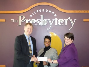 WEEE's Executive Director Alice Williams, center, receives SDOP funding from Sheldon Sorge, general minister, and Carla Campbell, stated clerk.