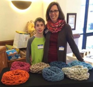 Jen Baker and her son Ryan sell some of the scarves Jen makes for The Scarf Farm, which raises money for a Romanian women's shelter for survivors of human trafficking.