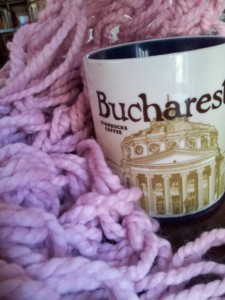 A scarf is nestled against a mug depicting a building in Bucharest where Jen Baker found a strong connection to a women's shelter.