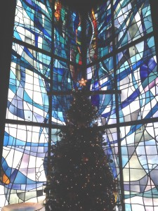 A stained-glass window is the backdrop for a Christmas tree at Church on the Mall in Plymouth Meeting.