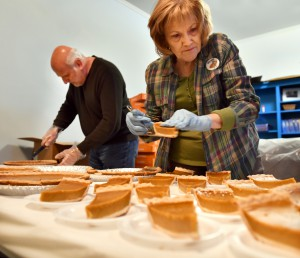 Fifty pumpkin pies are sliced and placed on plates, ready for whipped topping.